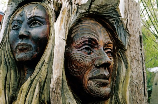 Maori carvings of a man and a woman's face - New Zealand
