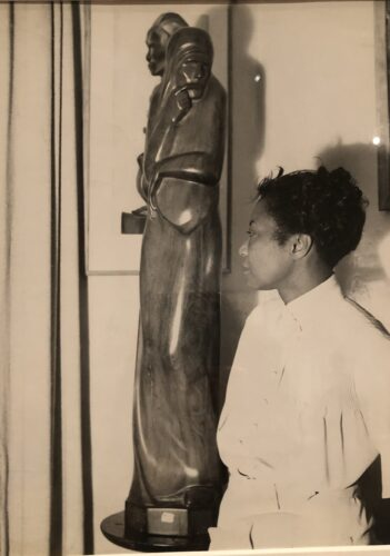 Augusta Savage poses with her sculpture